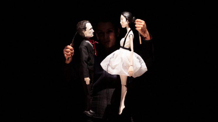 Fotografia de duas marionetas seguras por alguém na penumbra, dois bonecos de um homem e uma mulher, face a face