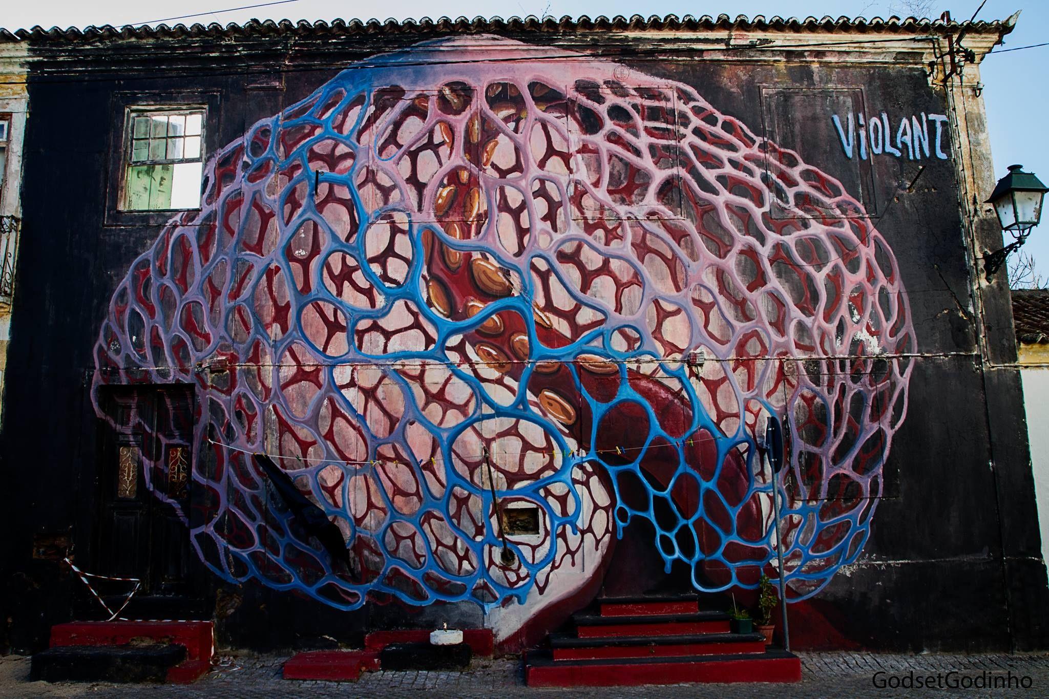 Fotografia de mural de arte urbana em Abrantes. Desenho mostra um rede como de um cérebro, em enorme escala, e surge uma escada para entrada.