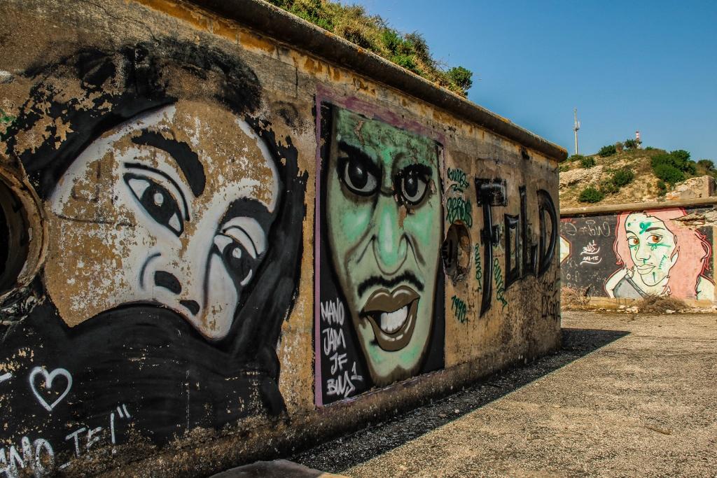 Mural compinturas de dois rostos nos fortes da trafaria
