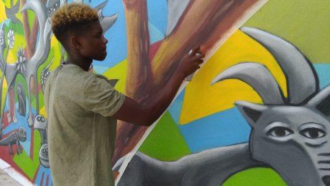fotografia de jovem a pintar um mural de arte urbana no bairro do vale da amoreira