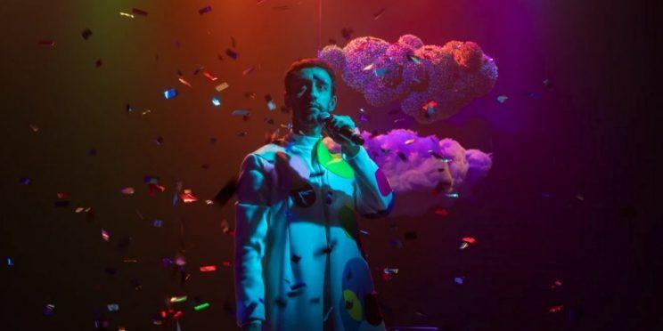 um ator segura o microfone num palco