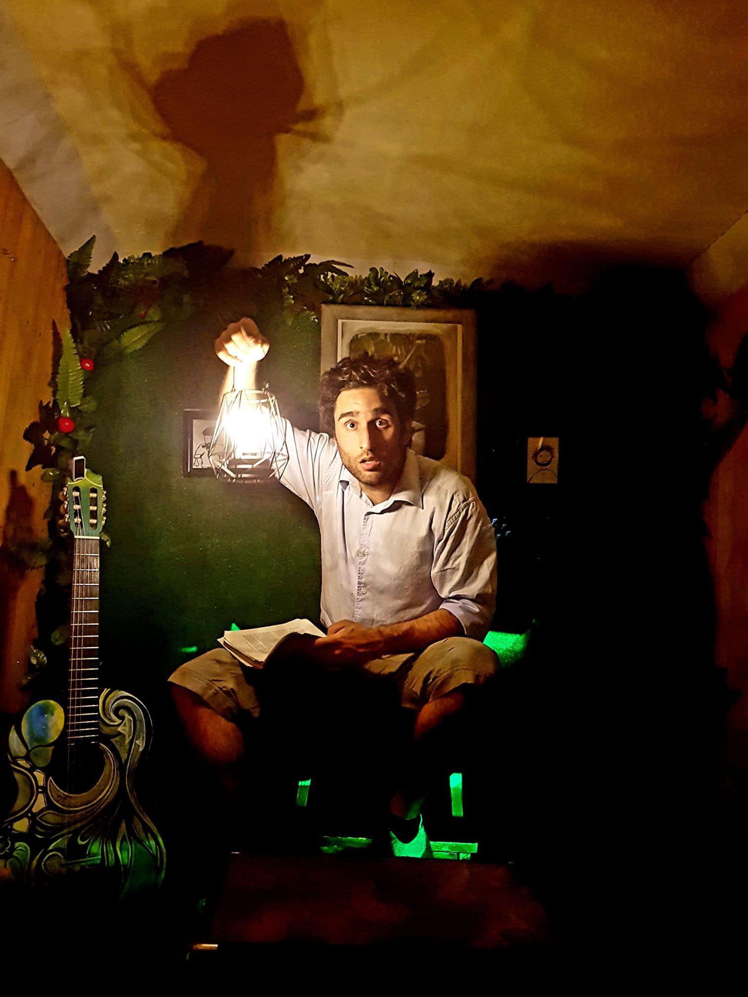 um actor segura numa lamparina em cena